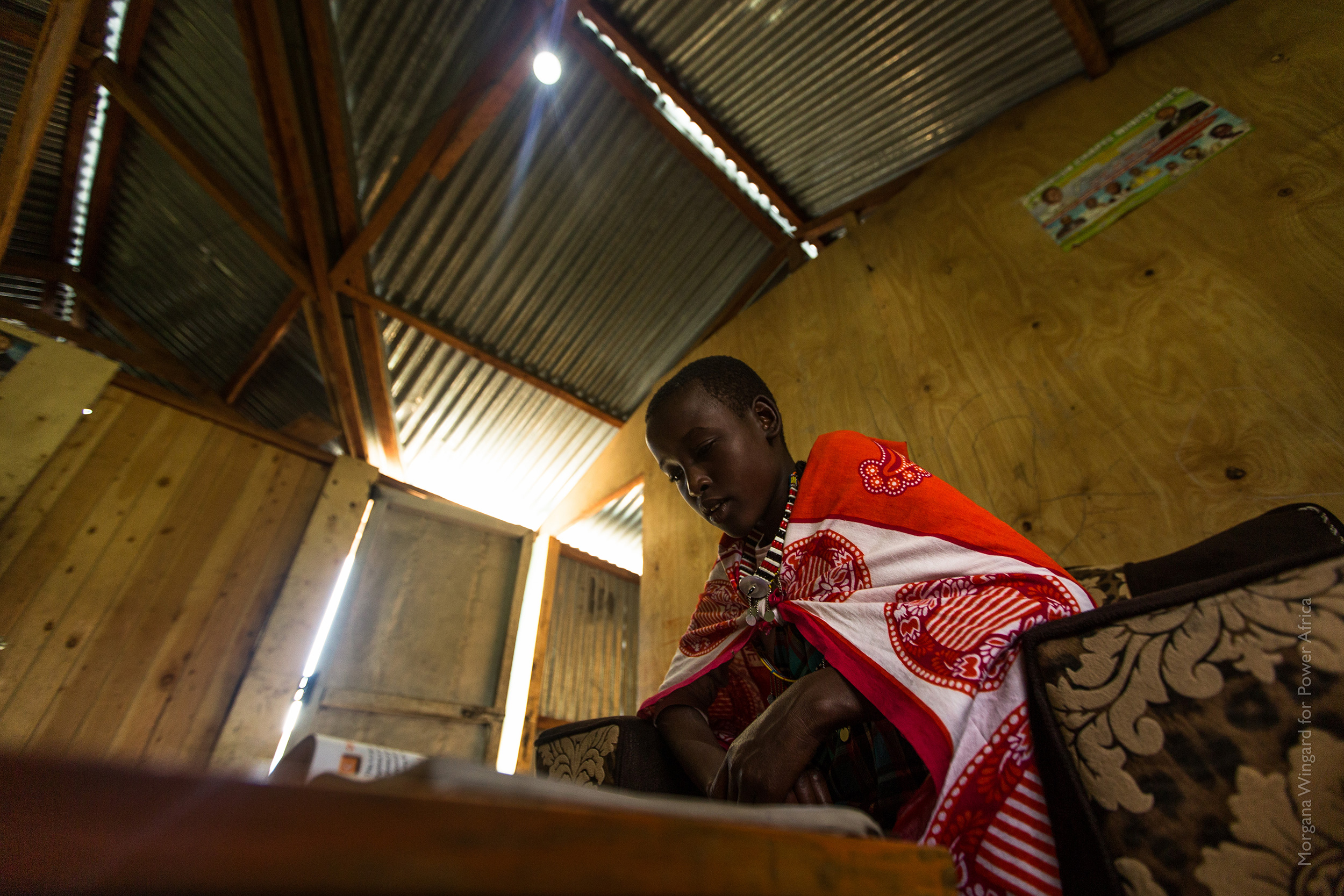 Nancy, 14, uses her family's M-KOPA solar powered light to study by at night