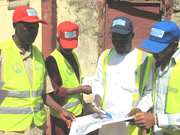 Surveyors review a map showing households selected to take part in the survey.