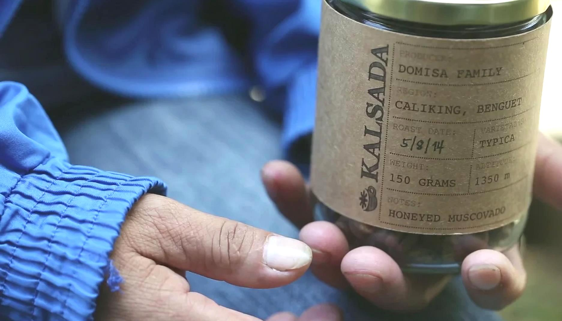 A farmer holds a jar of roasted Kalsada coffee beans that came from her farm.