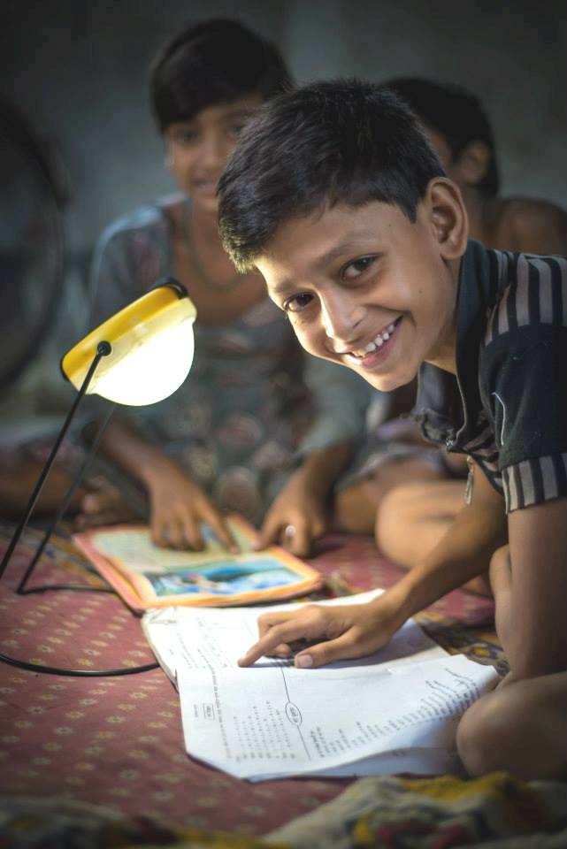 Sundar Mondal, the child of a DCBS client, uses the family's solar lamp to do his homework.