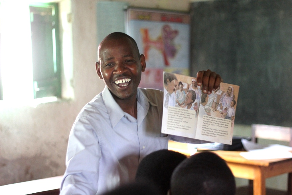 Celestin Ntirushwa, a teacher mentor, works with teachers on how to use new storybooks in their classrooms.