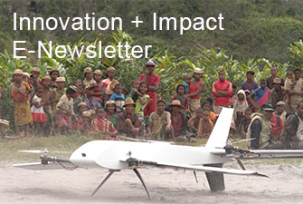Photo of villagers gathered around a UAV on the ground. Innovation + Impact E-Newsletter