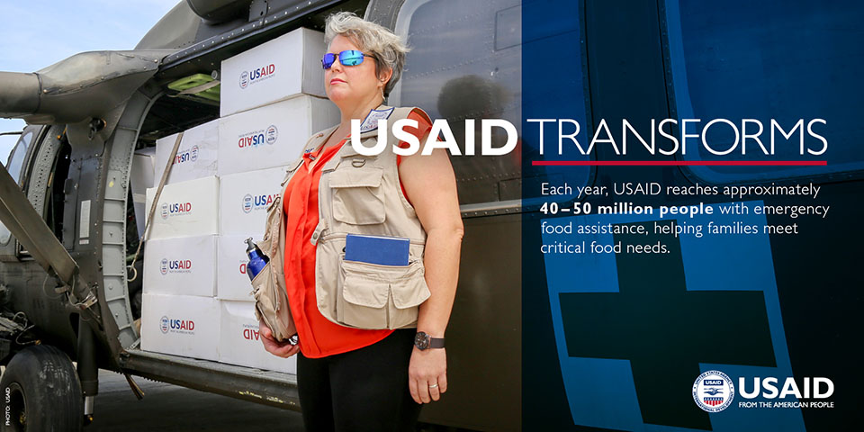Photo of an aid worker next to helicopter. USAID Transforms. Each year, USAID reaches approximately 40-50 million people with emergency food assistance, helping families meet critical food needs.