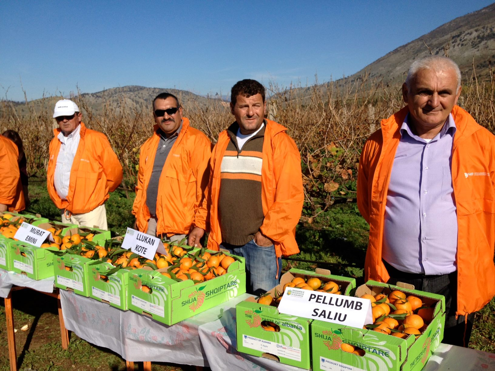 Men in orange coats stand behind displays of tangerines