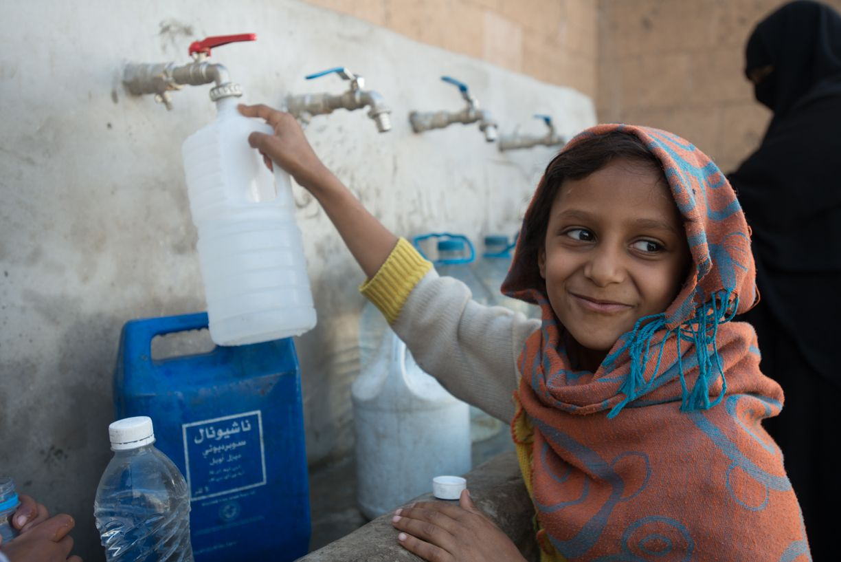 Aaliyah, a 7-year-old IDP, fetches clean water from a newly rehabilitated water.