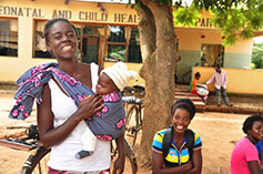 A mother stands holding her baby in a sling in front of her.