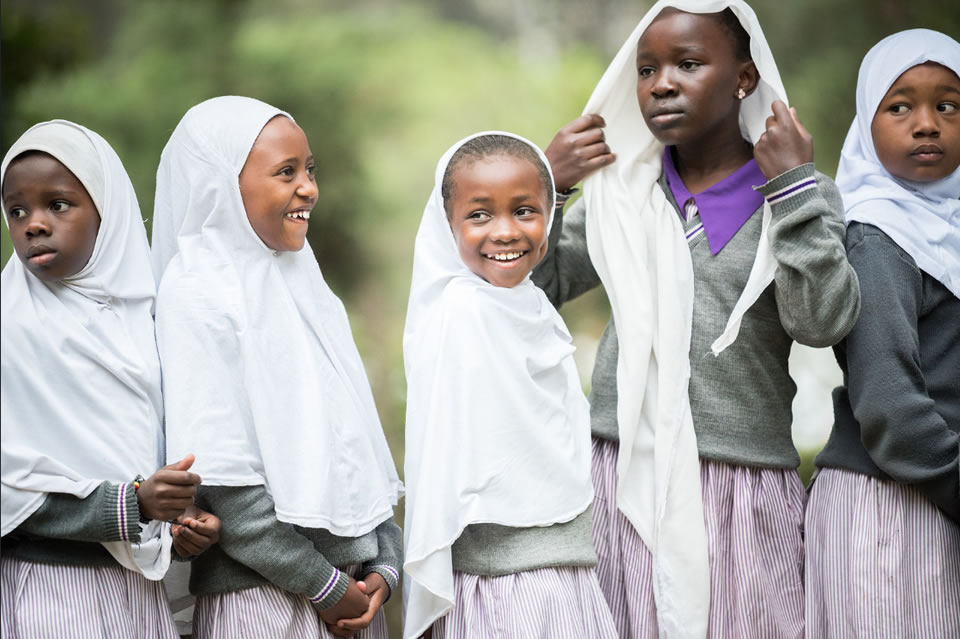A group of young girls in headscarves, smiling. Photo credit: Albin Hillert/WCC