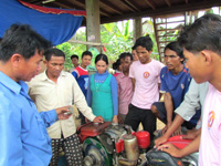 Farmers learn how to change the oil of a hand tractor in Pursat province.