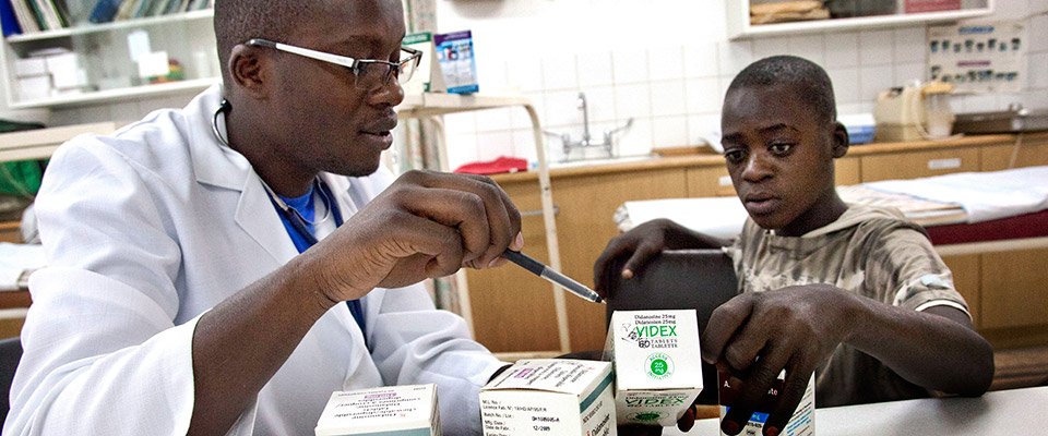 Researcher showing young boy HIV treatment drugs