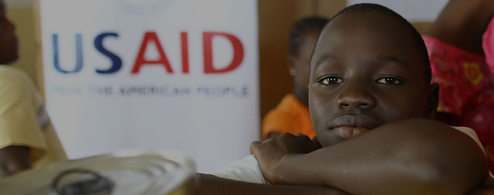 a boy sits in front of a USAID banner