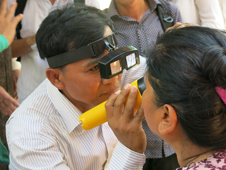 A doctor checks the eyes  of a woman in Cambodia