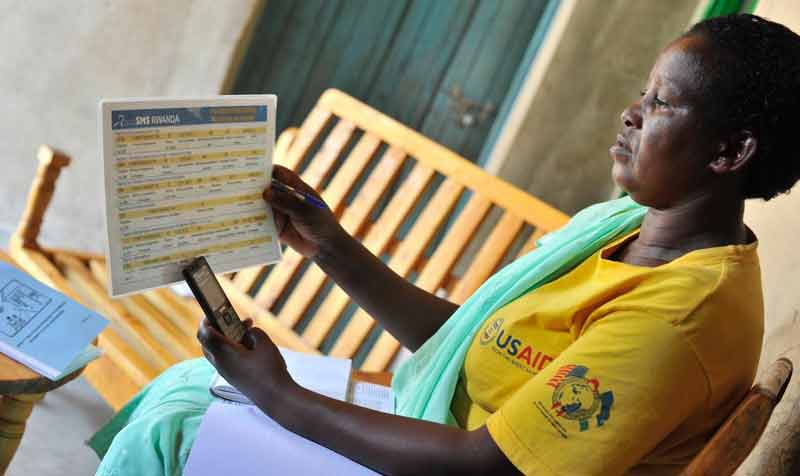 At the end of her visit, Community Health Worker Athalia Mukamusoni sends the health information she collected to a national dashboard that keeps track of mother and children's health at the community level.