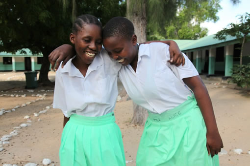 Two young girls laugh and throw their arms around each other.