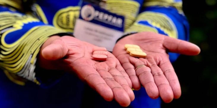 Hands holding a set of two different pills.