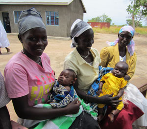 A community health promoter in South Sudan sits with with her neighbors and their babies