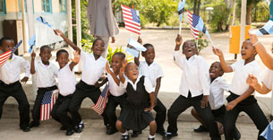 School children in Botswana wave flags for World AIDS Day.