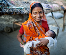 Smiling woman from India holding her baby