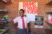 A young girl poses by a sign reading DREAMS 72 hours, b.v. desk