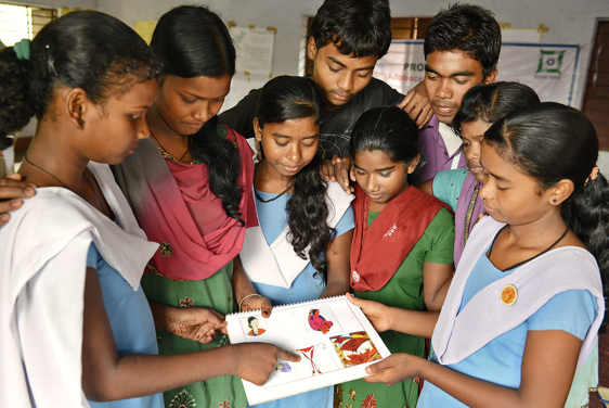 Adolescents gathered around looking at a document