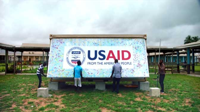 Men open up a USAID mobile laboratory