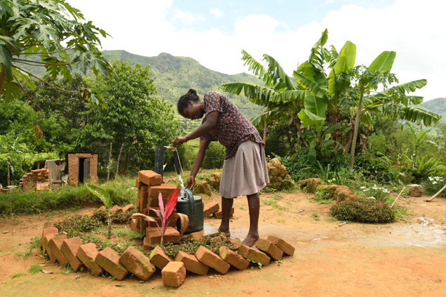 A woman uses a hand pump for clean water.