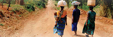 Photo of three with women with supplies on their head.