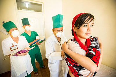 A woman is examined by a doctor for TB