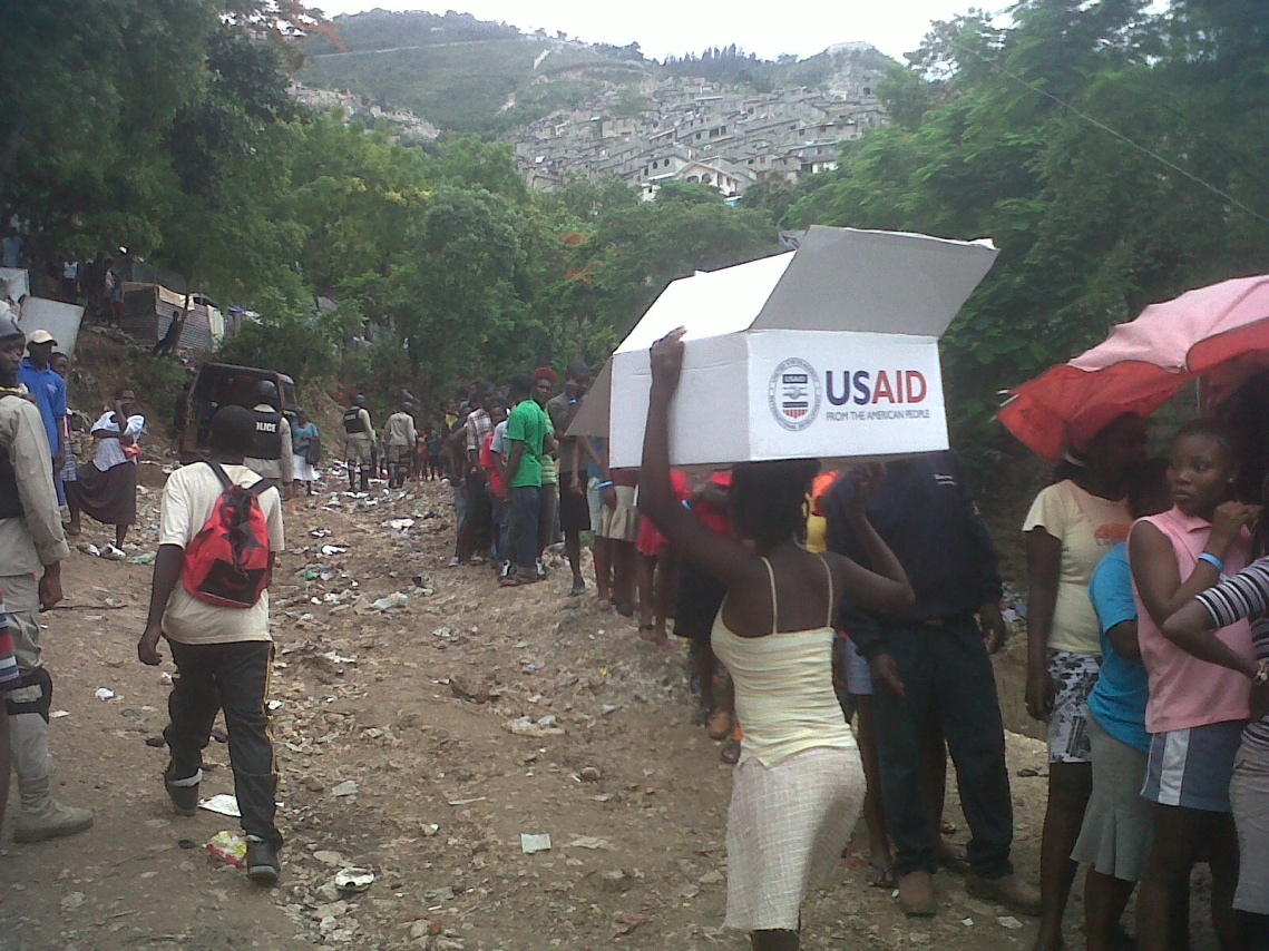 Residents of an earthquake displacement camp near Petionville in metropolitan Port-au-Prince receive emergency relief