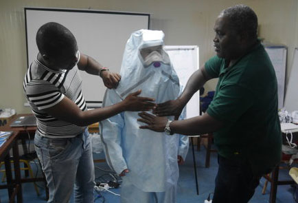 Two men help put protective clothing on a third person.