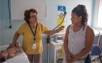 A medical professional examines a child while speaking to a mother.