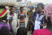 A group of women in a market discuss health issues. Photo credit: Yakuba Yusuf/Project HOPE