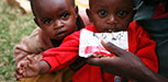 Two children receive supplementary food from a packet