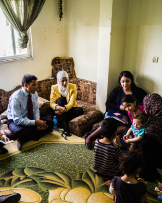 USAID Administrator Rajiv Shah with Syrian refugee family in their home in Jordan