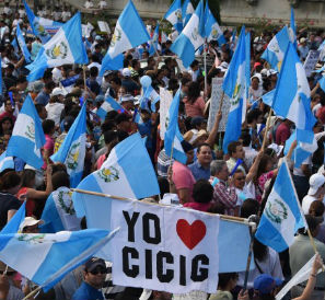 People hold national flags and a sign reading I love CICIG (International Commission Against Impunity in Guatemala) as they take part in a Aug. 22 demonstration in Guatemala City demanding President Otto Perez's resignation. / Johan Ordonez, AFP