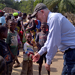 USAID Global Water Coordinator Christian Holmes congratulating children in forest community in Liberia on reaching open defecati