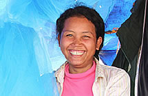 A woman smiles from beneath mosquito nets