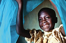 A child smiles beneath mosquito nets