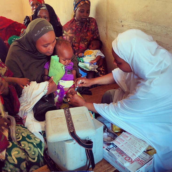 Nigerian women hold their young children while they are getting polio vaccinations.