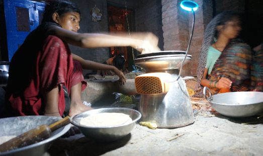 In Gheghta Village, Poona cooks chapatis on a HomeStove under USB-powered light.