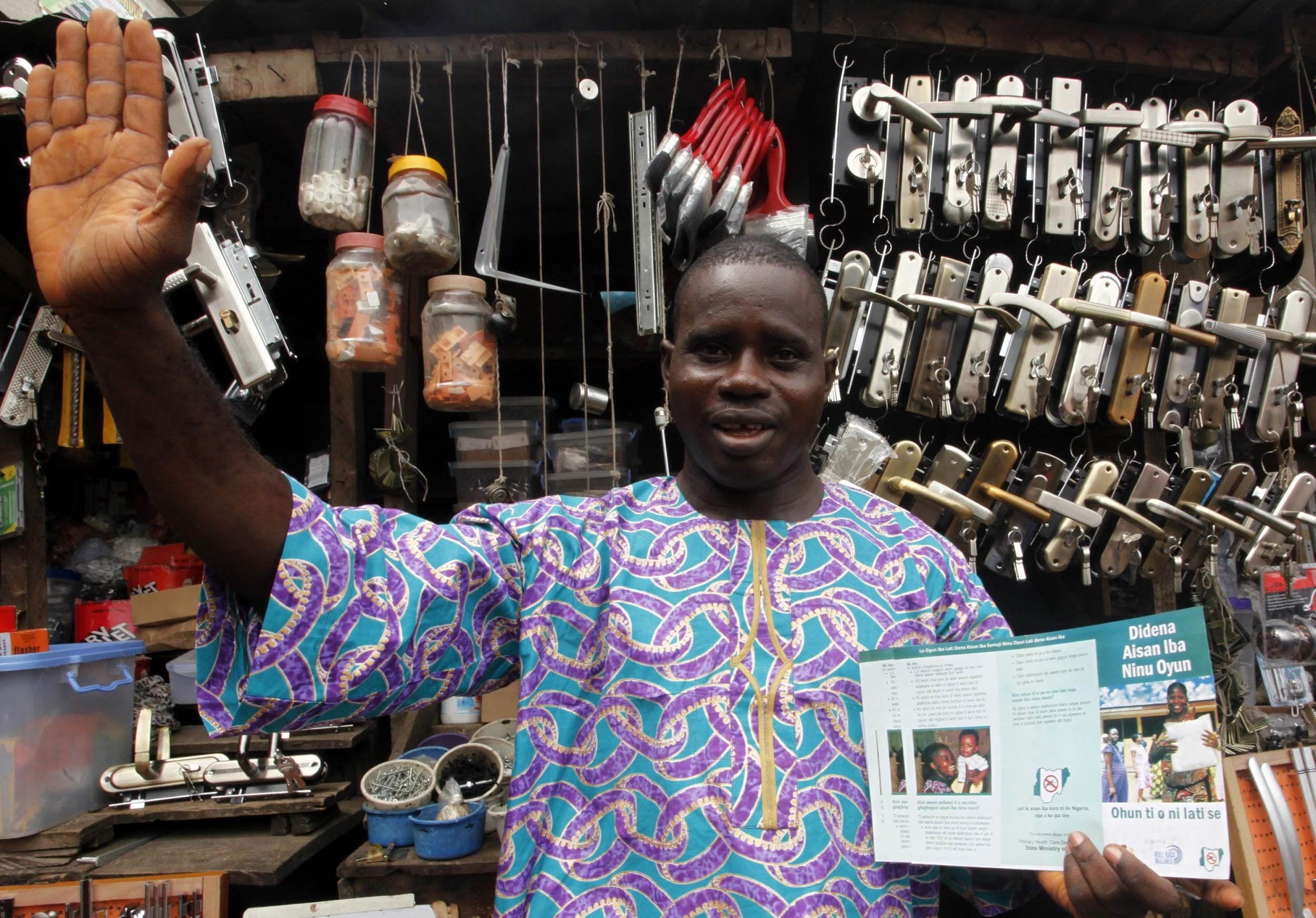 A store owner in Nigeria shows a malaria prevention flyer.