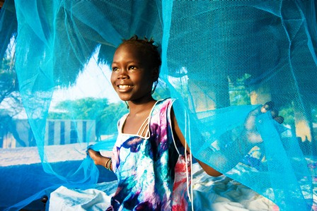 Young girl with malaria bed net.