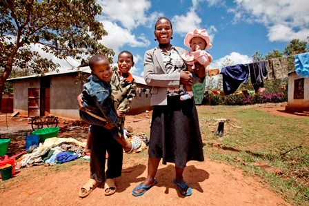 A happy family does laundry outside their home in Tanzania. Photo Credit: EGPAF/James Pursey