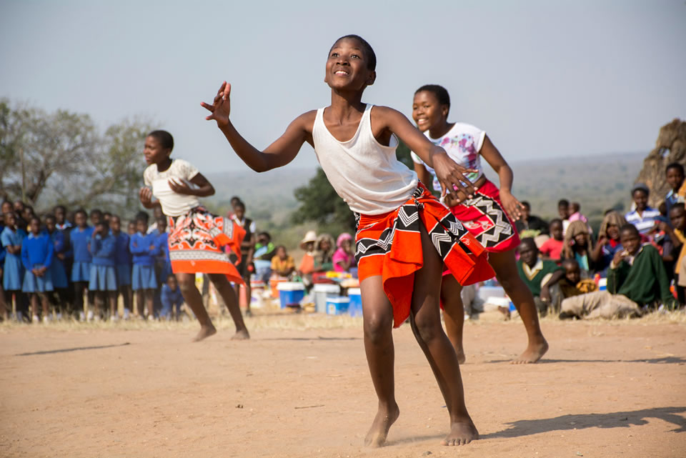 A group of young African women dance together. Eric Bond/Elizabeth Glaser Pediatric AIDS Foundation