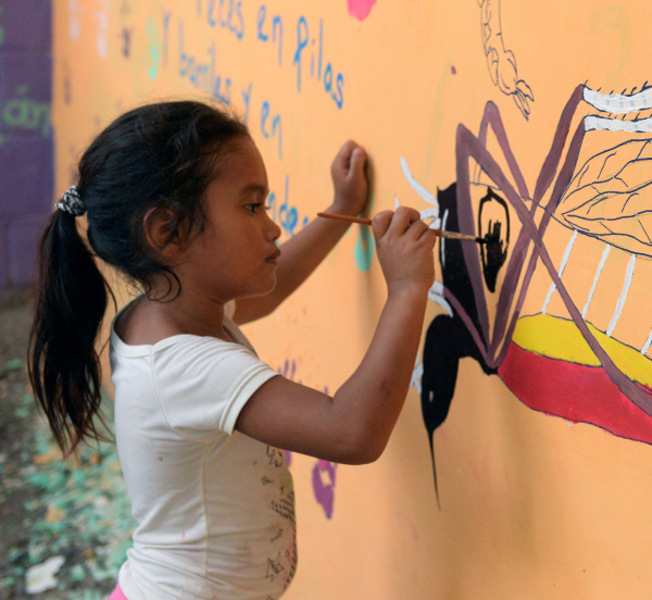 young girls painting a mural of a mosquito on a wall