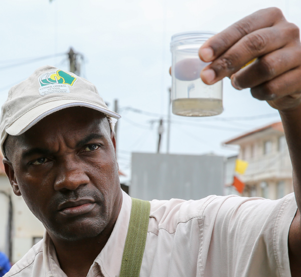 man holding sample of water