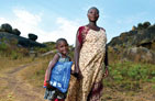 A mother stands with her child who is holding a bednet