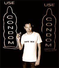 Photo of a man holding a condom and wearing a shirt say that says 'safe sex'.