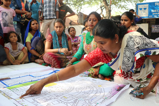 In India, a woman points to an area on a map