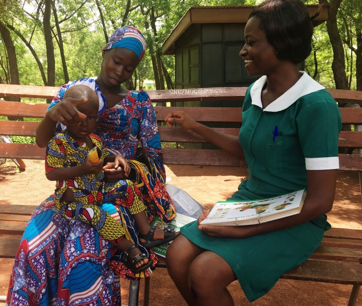A Ghana health worker discusses breastfeeding with a woman holding a young child.