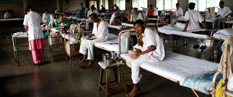 Men on cots in a TB clinic.